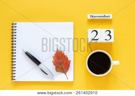 Autumn composition. Wooden calendar November 23 cup of coffee, empty open notepad with pen and yellow oak leaf on yellow background. Top view Flat lay Mockup Concept Hello November stock photo