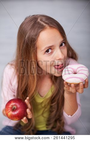 Young teenager girl tempted by the sugary food - craving the donut with sugar coating over an apple stock photo