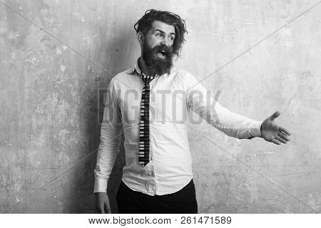 Business fashion and beauty. Guy hold hand for handshake. Man with long beard and mustache on happy face. Fashion model with stylish hair on textured wall background Hipster in shirt and musical tie. stock photo