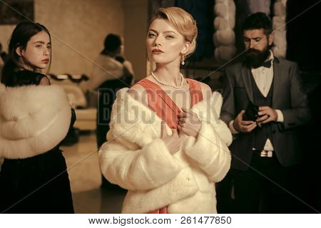 Purchase, business, moneybags. People among fur coat, envy, betrayal, luxury. Fashion, beauty, winter, fur. Date, family love man women Women in fur coat with man shopping seller and customer stock photo