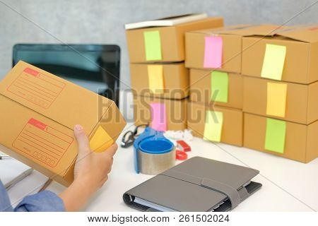 startup small business owner hold cardboard box at workplace. freelance woman entrepreneur seller prepare parcel box for delivery product to customer.  Online selling, e-commerce concept stock photo