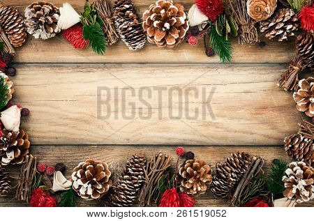 Winter background with rustic Christmas garland.Using pine cones,dried leaves and berries, twigs and