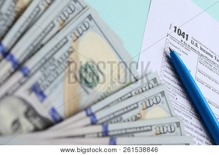 1041 tax form lies near hundred dollar bills and blue pen on a light blue background. US Income tax return for estates and trusts stock photo