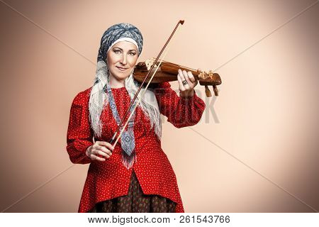 Elderly native woman in a national costume plays the ancient violin. stock photo