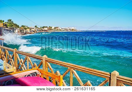 Watch the strong foaming waves on Aqaba Gulf, enjoying free time in local coastal cafe, Dahab, Sinai, Egypt. stock photo