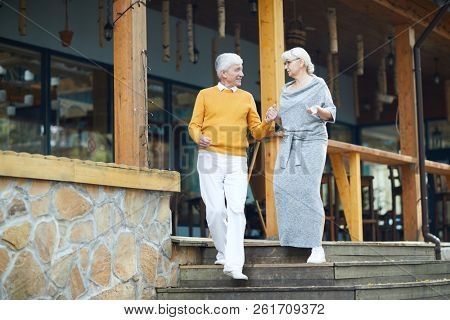 Smiling handsome senior gentleman in yellow sweater supporting lady and holding her hand while they moving down stairs and chatting at veranda stock photo