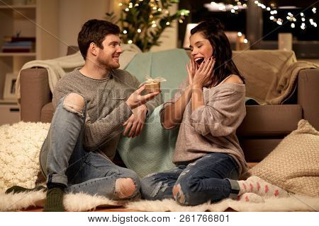 hygge, holidays and people concept - happy couple with gift box at home stock photo