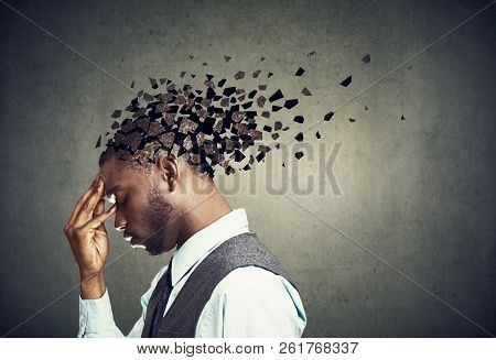 Memory loss due to dementia or brain damage. Side profile of a sad man losing parts of head as symbol of decreased mind function. stock photo