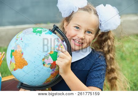 Portrait of a beautiful young Schoolgirl on the red wooden background witn big letters ABC. Farewell Bell. day of knowledge. beginning of the school year. stock photo