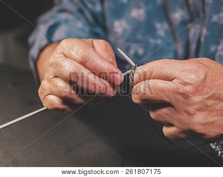 Close up hands with wrinkles of elderly woman knitting wool yarn sweater or scarf for the winter. Grandmother knits at home. Process of making clothes. Hobby concept. stock photo