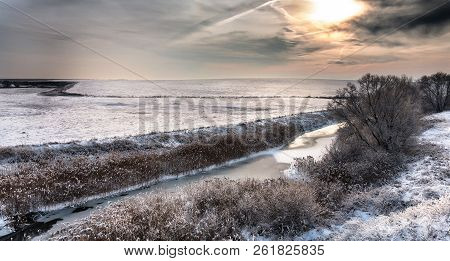 River landscape covered by fresh snow during Winter sunrise sunset stock photo