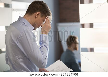 Nervous sweaty speaker preparing speech wiping wet forehead with stock photo