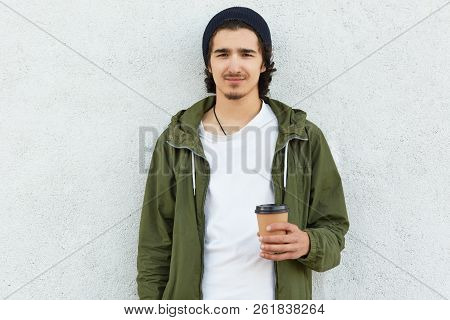 Waist up shot of bearded cool curly boy in black hat, green jacket, dtinks coffee or cappuccino, poses against white concrete wall alone, enjoys spare time. People, youth and lifestyle concept. stock photo