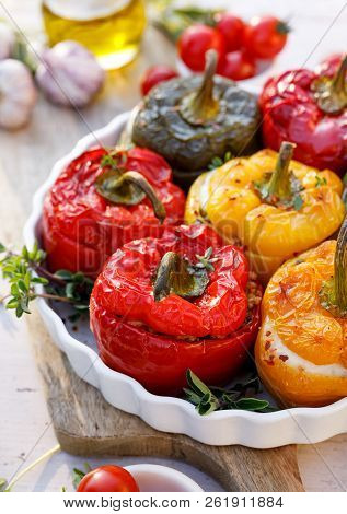 Roasted bell pepper with mushroom, rice, cheese and herbs filling in a baking dish on a white wooden table. A healthy and delicious vegetarian food. stock photo