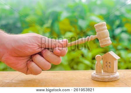 The judges gavel hovered over the wooden and human figure. Concept of justice and litigation. The decision of the fate of the defendant and property. Protection of rights and confiscation of property stock photo