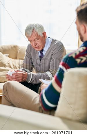 Sad handsome elderly man with gray hair holding napkin and talking to psychologist about his problems in coy office, he visiting shrink stock photo