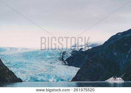 View of Holgate Glacier in Kenai Fjords National Park - unidentifiable ship sails close to the glacier stock photo