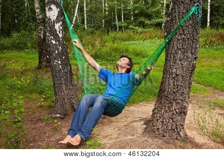Barefooted man sits in hammock suspended between two thik birches, head thrown back, eyes closed stock photo
