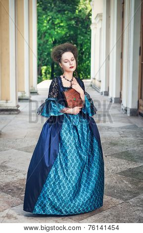 Beautiful young woman in blue medieval dress with book outdoor stock photo