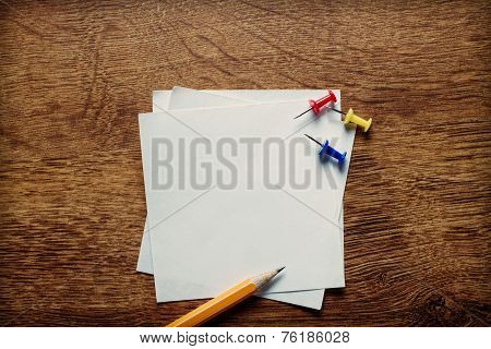 Stack of small square blank white memo pages with a pencil for jotting notes and reminders and thumbtacks to attach to a notice board overhead view on a wooden desk stock photo