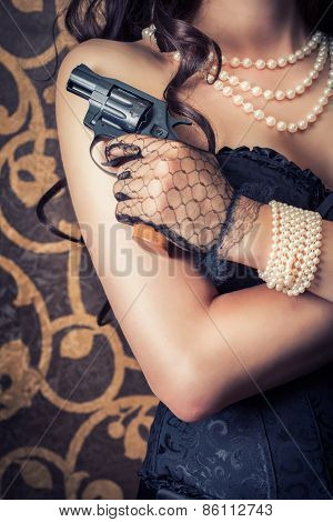 woman wearing black corset and pearls and holding a gun against retro background stock photo