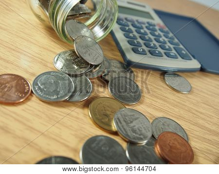 Financial business, pile of coins, Thai Money In Glassware, Calculator On Wood Background