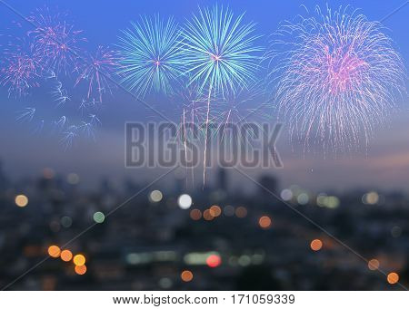 Colorful fireworks on blurred skyscrapers with city bokeh lights illuminated at twilight. Abstract New Year holiday or party background