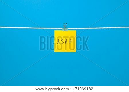 "Yellow paper note on the string with text ""ASAP"" over colorful background stock photo"