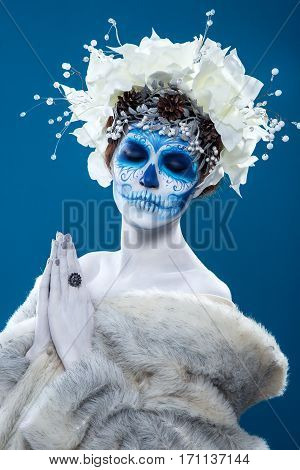 Santa Muerte concept of body art. Young woman with short curly hair and creative visage. White flowers in hair, make up, portrait at blue background, wearing fur coat.