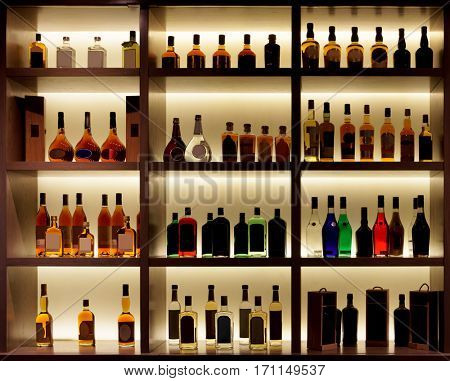 Various alcohol bottles in a bar, back light, all logos removed stock photo
