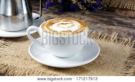 Heart latte art. Cappuccino coffee. A cup of latte, cappuccino or espresso coffee with milk put on a wood table with dark roasting coffee beans. Drawing the foam milk on top. stock photo