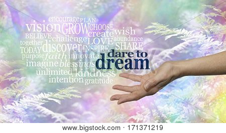 Dare to Dream word cloud - Female hand outstretched palm up on a rainbow woodland background and the words DARE TO DREAM floating above surrounded by a relevant word cloud stock photo