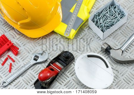 Carpentry DIY tools and safety gear including a hammer face mask hand plane an adjustable wrench rawl plugs hard hat vest metal rule and a box of screws on steel tread plate. stock photo