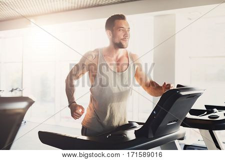 Young happy handsome man with tattoo in fitness club. Cardio workout, running on treadmill. Healthy lifestyle, guy training in gym. Flare effect stock photo