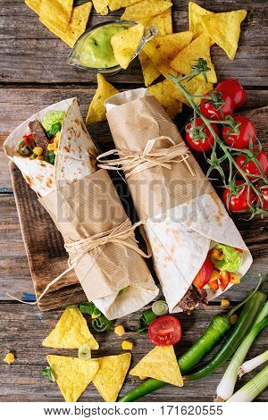 Mexican style dinner. Two papered tortillas burrito with beef and vegetables served with vegetables nachos chips and guacomole sauce over old wooden background. Flat lay stock photo