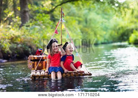 Kids dressed in pirate costumes and hats with treasure chest spyglasses and swords playing on wooden raft sailing in a river on hot summer day. Pirates role game for children. Water fun for family. stock photo