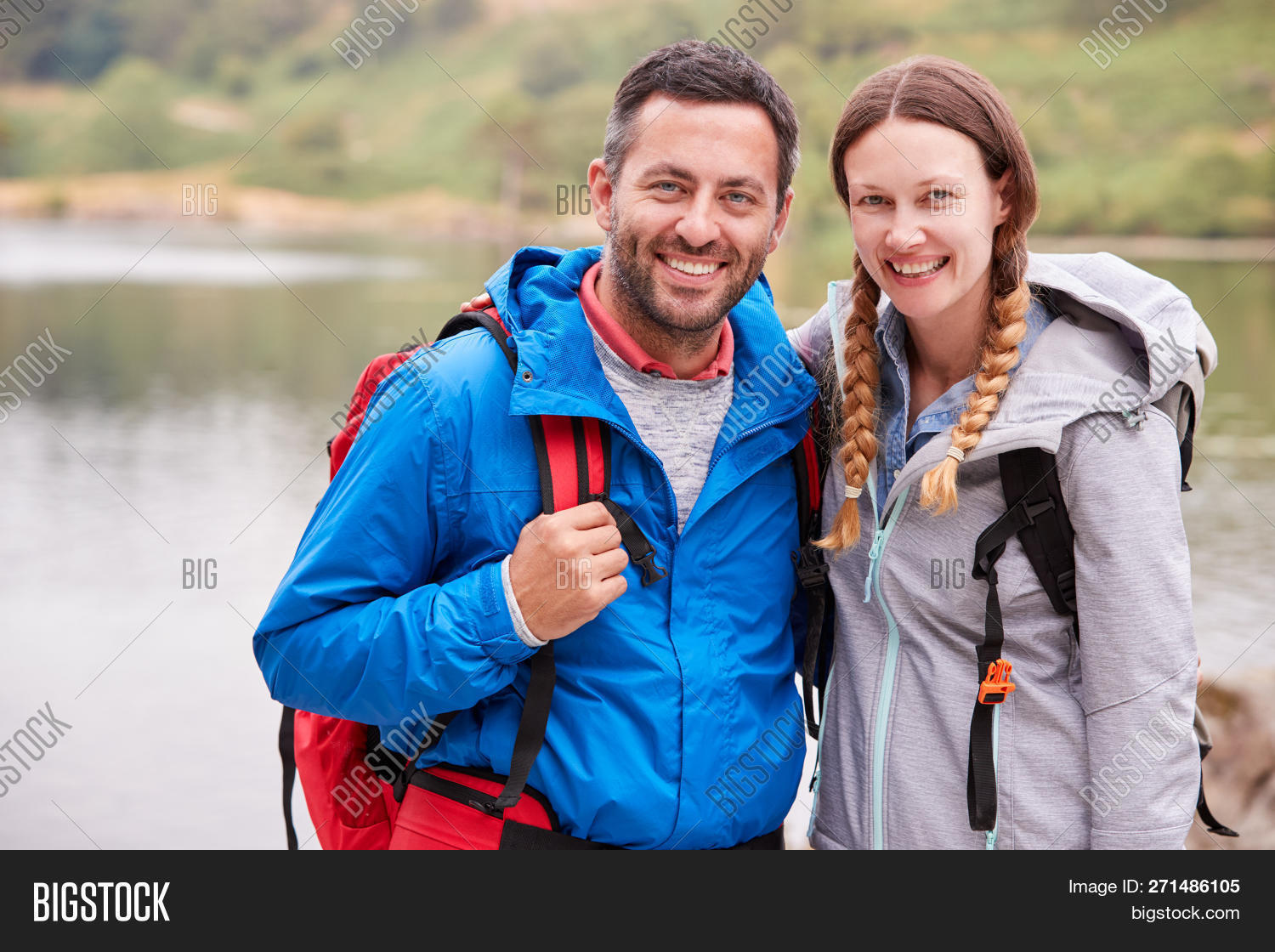 30s,40s,active lifestyle,adults,adventure,arms around,backpacks,bonding,braids,camping trip,casual clothing,caucasian,close up,copy space,countryside,couple,day,embracing,exploring,focus on foreground,free time,front view,getting away from it all,happy,holiday,horizontal,lake,lake district,looking at camera,man,middle aged,millennial,outdoors,smiling,spring,standing,summer,sunlight,the great outdoors,togetherness,tranquility,two people,uk,vacation,waist up,waterproof jacket,woman,young adult
