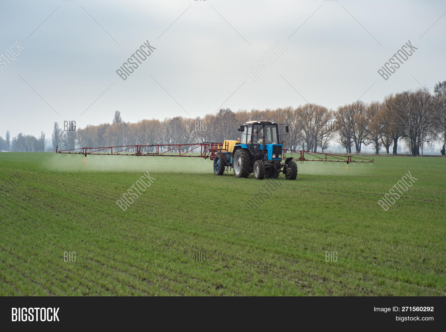 farm tractor spraying agrochemical or agrichemical over young grain field in most cases agrichemical refers to pesticides like insecticides herbicides fungicides and nematicides