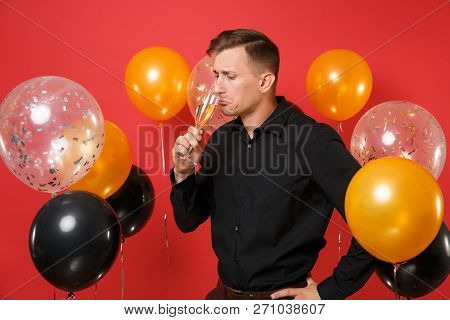 Distrustful young man in black classic shirt holding, sniffing glass of champagne on bright red background air balloons. International Womens Day Happy New Year birthday mockup holiday party concept. stock photo