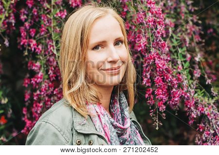 Outdoor portrait of beautiful blond woman, posing outdoors, wearing khaki color parka and pink scarf stock photo