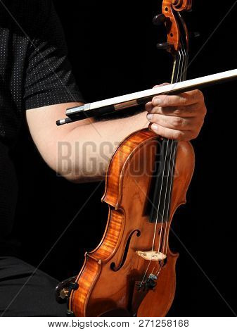 Close-up Of A Musician Holding His Violin And Bow. The Instrument Rests On His Leg. Black Background