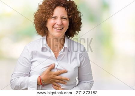 Beautiful middle ager senior businees woman over isolated background Smiling and laughing hard out loud because funny crazy joke. Happy expression. stock photo