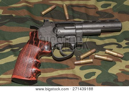 Revolver on camouflage background. Pneumatic gun 4, 5 mm stock photo