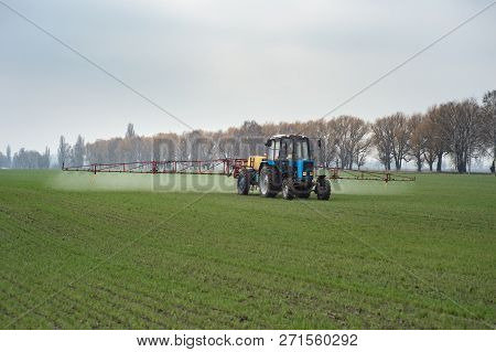 farm tractor spraying agrochemical or agrichemical over young grain field in most cases agrichemical refers to pesticides like insecticides herbicides fungicides and nematicides stock photo