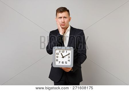 Upset young business man in classic black suit, shirt putting hand on cheek, holding square clock isolated on grey background in studio. Achievement career wealth business concept. Mock up copy space. stock photo