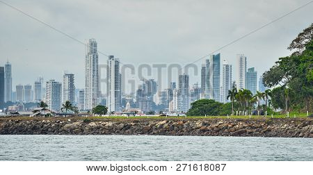 Hot humid day in Panama city as another rainstorm brews quickly over city skyline.  Tall buildings shimmer in heatwaves rising in humid air.  People walking on Panama Canal rock wall jetty park in foreground. stock photo
