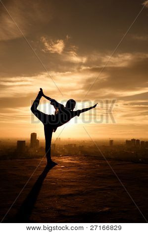 girl does yoga at sunset on top of a building stock photo