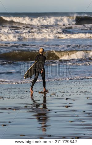 Young female surfer and her reflection walking along the shoreline at Ventura Surfer's Point in California, USA on December 1, 2018.  Last bit of the northwest swell bringing fun waves to the coast. stock photo