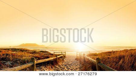 Coucher de soleil panorama hdr d'une plage près de cape town, afrique du sud. montagne de la table peut être vu dans la dista