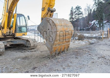 Excavator work tool close up shot near a frozen river at wintertime. stock photo